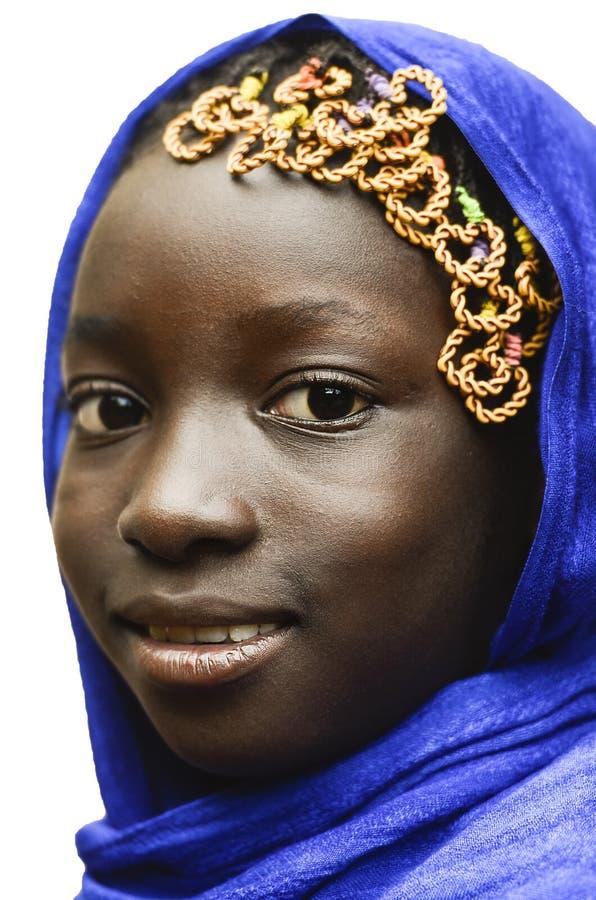 Herrliches lächelndes afrikanisches Schulmädchen verschleiert von einem blauen typischen Afrikaner Hijab lizenzfreie stockbilder