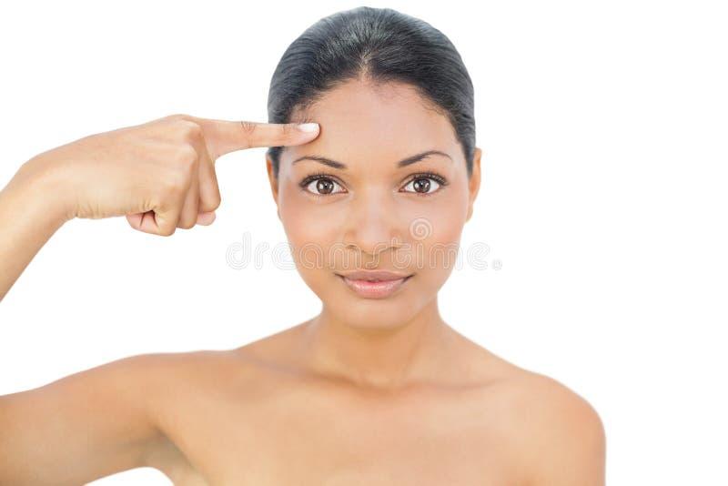 Herrliches schwarzes behaartes Modell, das auf ihre Stirn zeigt stockbild