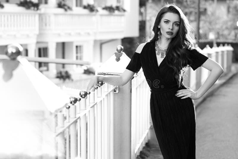 Herrliches weibliches Modell im schwarzen Kleid mit Ausschnitt schultert stockbilder