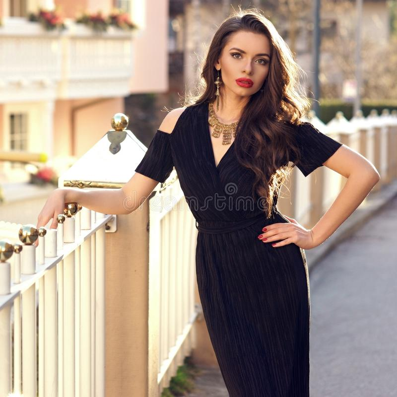 Herrliches weibliches Modell im schwarzen Kleid mit Ausschnitt schultert lizenzfreies stockbild