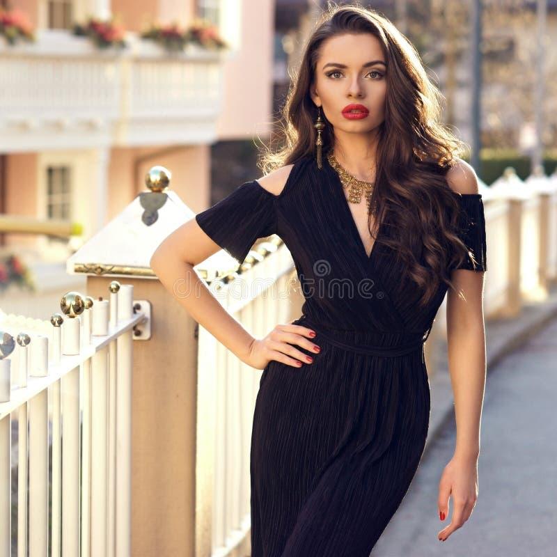 Herrliches weibliches Modell im schwarzen Kleid mit Ausschnitt schultert stockbild