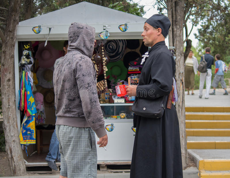Hersonissos, Crimea - September 03, 2011: Monk collecting donations for the construction of the temple talking to the layman stock photos