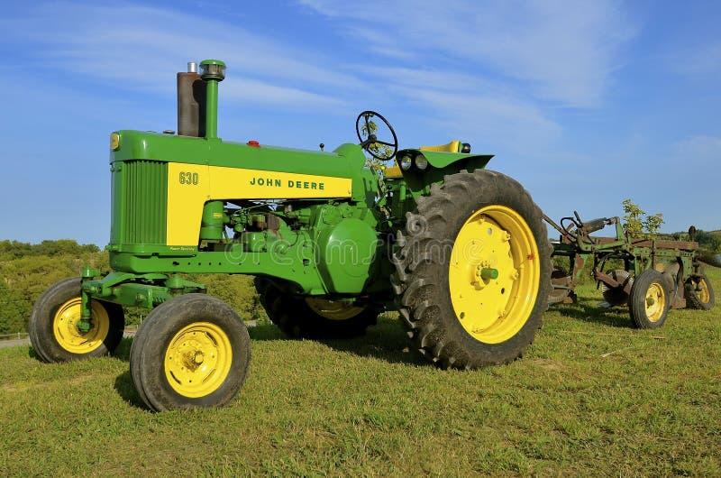 Hersteld John Deere 630 tractor en reisploeg stock foto