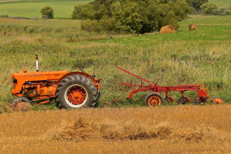 Herstelde die de tractortractor van Minneapolis Moline aan een ploeg van de drie bodemreis wordt vastgehaakt stock afbeeldingen