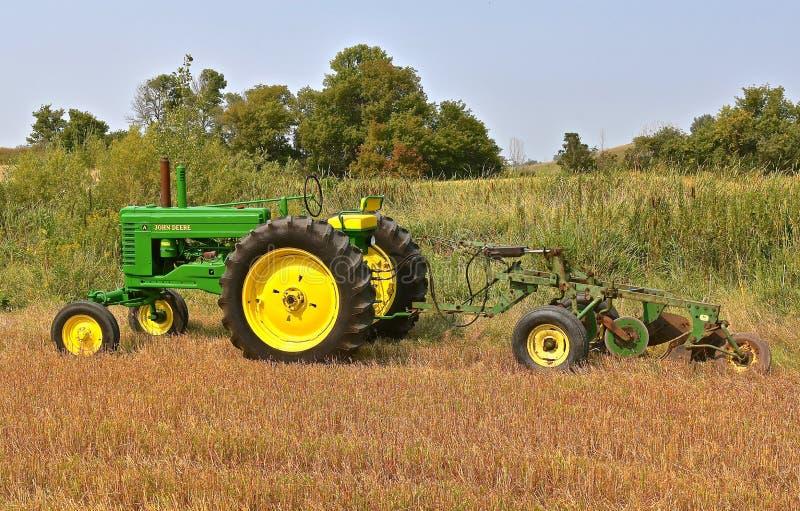 Herstelde die John Deere-tractortractor aan een ploeg van de vier bodemreis wordt vastgehaakt royalty-vrije stock fotografie