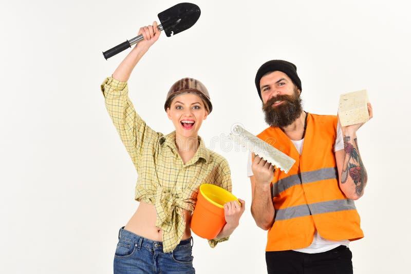 Hersteller met meisje, exemplaarruimte Glimlachende die vrouw in helm over vernieuwing wordt opgewekt Bouwers met baksteen, schop stock foto's