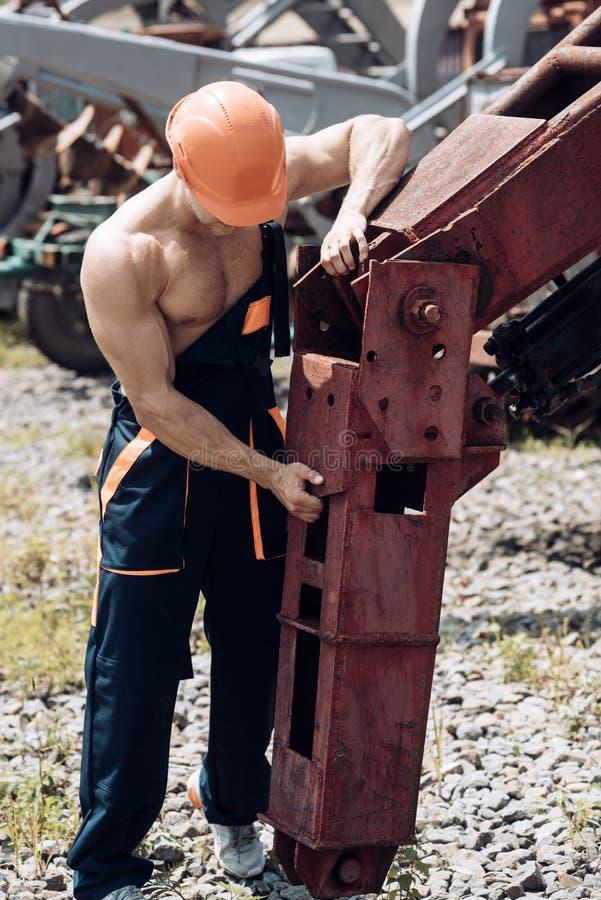 Herstellerconcept Bekwame hersteller op het werk Het zware materiaal van de herstellermoeilijke situatie Machineshersteller in ee stock fotografie