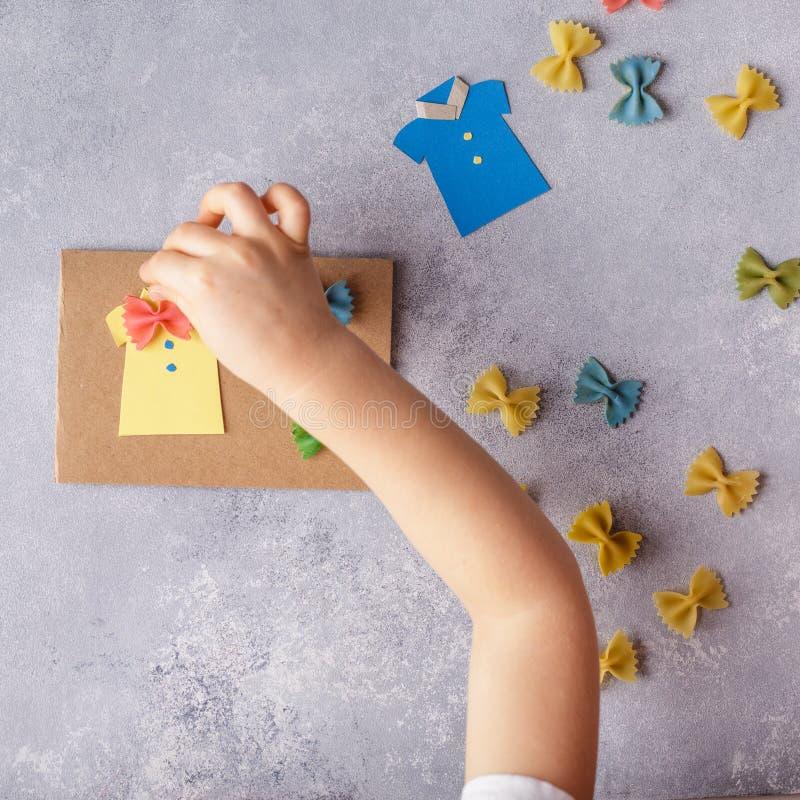 Herstellung der Grußkarte für Vatertag Hemd mit Schmetterling von den Teigwaren Karte vom Papier schnurrbart Kunstprojekt der Kin stockbild