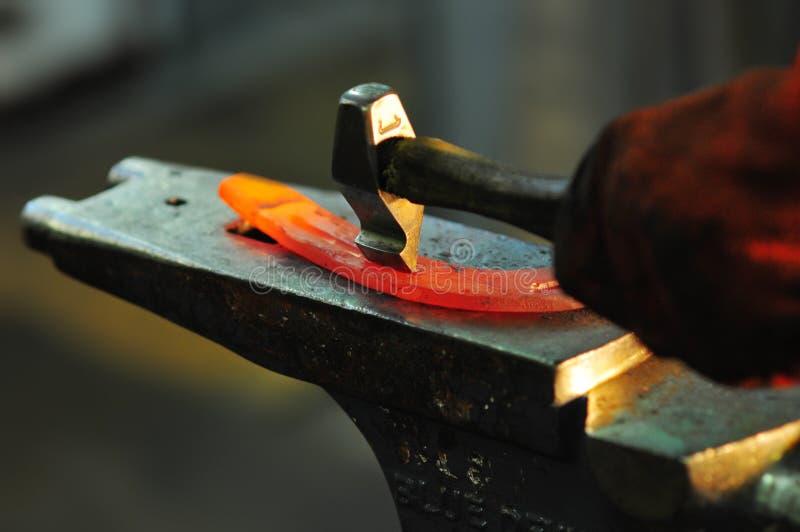 Herstellung des dekorativen Elements in der Schmiede auf dem Ambosse Das Glühen hämmern Stahl Schmied schmiedet ein heißes Hufeis lizenzfreie stockfotos