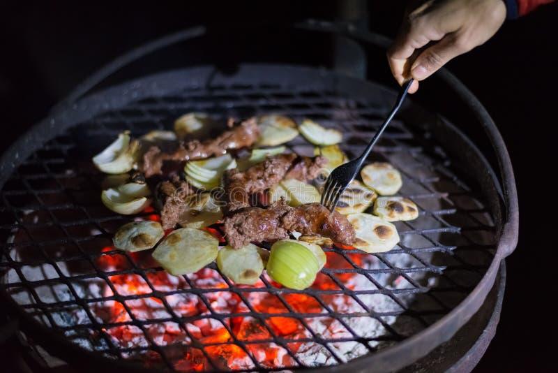 Herstellung des Grills nachts Menschliche Hand, welche die Gabel vereinbart Würste, Kartoffeln und Zwiebeln auf Grill hält Braai, stockbilder
