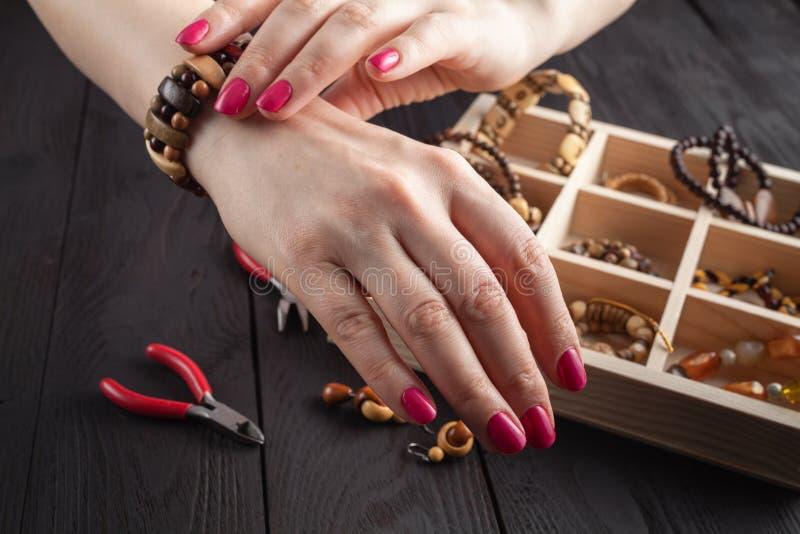 Herstellung des handgemachten Schmucks Frau, die ein selbst gemachtes Armband versucht stockfotografie