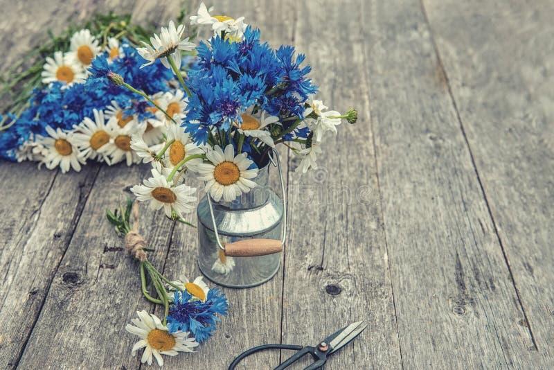 Herstellung eines Blumenstraußes von schönen wilden Blumen von Gänseblümchen und von Kornblumen auf dem Hintergrund des alten höl lizenzfreie stockfotos