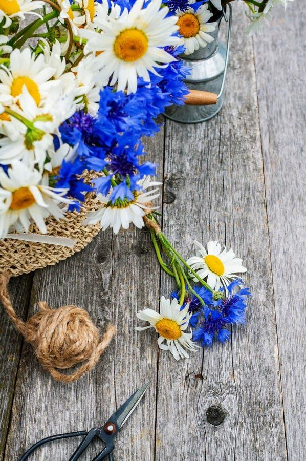 Herstellung eines Blumenstraußes von schönen wilden Blumen von Gänseblümchen und von Kornblumen auf einem hölzernen alten Hinterg stockfotos