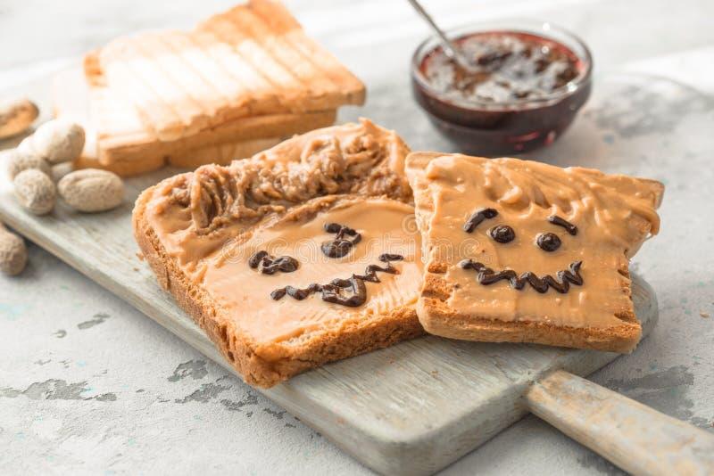 Herstellung von Erdnussbuttersandwichen mit Persönlichkeit! Spaßsmileygesicht an gezeichnet mit Stau Sahnige Erdnussbutter mit St stockfoto