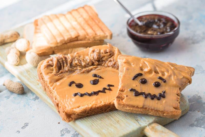 Herstellung von Erdnussbuttersandwichen mit Persönlichkeit! Spaßsmileygesicht an gezeichnet mit Stau Sahnige Erdnussbutter mit St lizenzfreie stockbilder