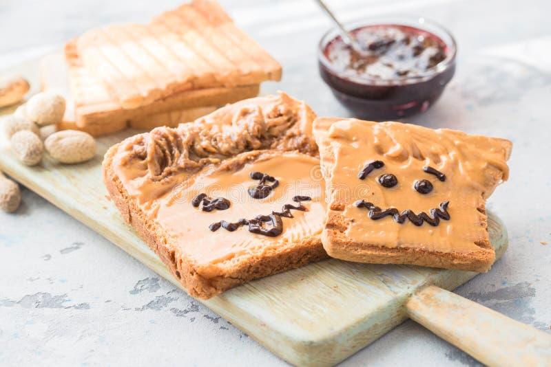 Herstellung von Erdnussbuttersandwichen mit Persönlichkeit! Spaßsmileygesicht an gezeichnet mit Stau Sahnige Erdnussbutter mit St stockfotografie