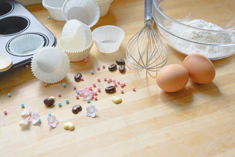 Herstellung von kleinen Kuchen, von Werkzeugen und von Bestandteilen auf einem hölzernen Küchenbrett, Kopienraum lizenzfreies stockfoto