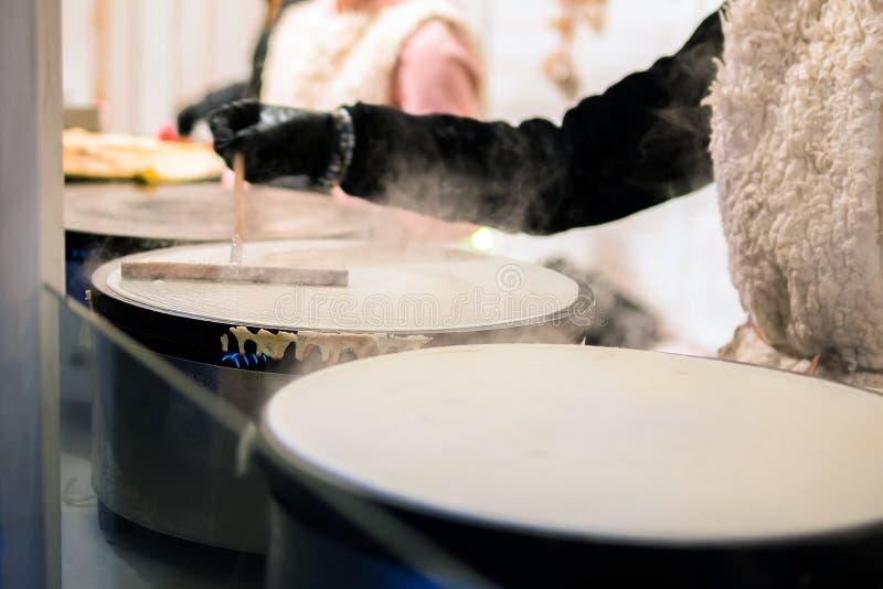 Herstellung von Krepppfannkuchen im Festival des freien Marktes angemessen Eine Hand stellt Krepps draußen auf einem Metallbratpf stockfotografie