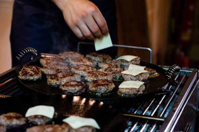 Hertevleeshamburgers op een barbecuegrill die worden gebraden stock foto