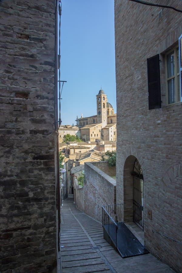 Hertogelijk die Paleis van Urbino van een steeg wordt gezien stock fotografie