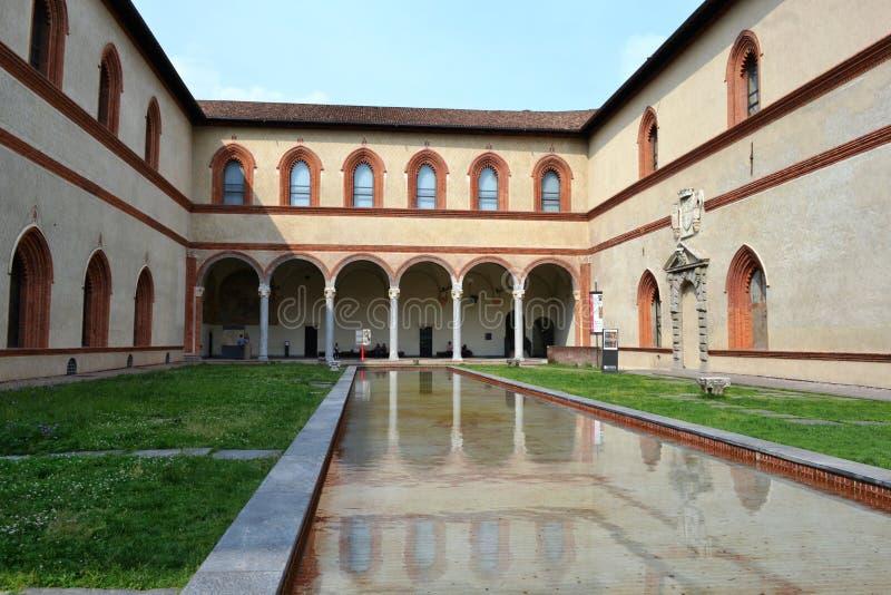 Hertogelijk Hof van Sforza-Kasteel in Milaan en zijn oude middeleeuwse die arcades, in het poolwater wordt weerspiegeld royalty-vrije stock foto