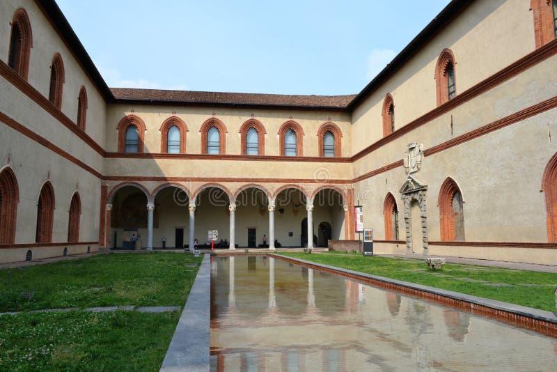 Hertogelijk Hof van Sforza-Kasteel in Milaan en zijn oude middeleeuwse die arcades, in het poolwater wordt weerspiegeld royalty-vrije stock afbeelding
