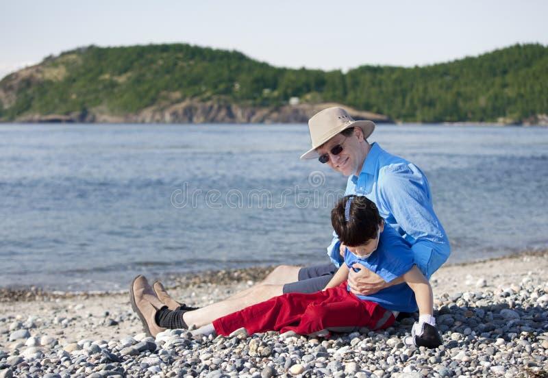 Hervorbringen Sie das Sitzen auf dem Strand, der mit untauglichem Sohn spielt lizenzfreies stockfoto