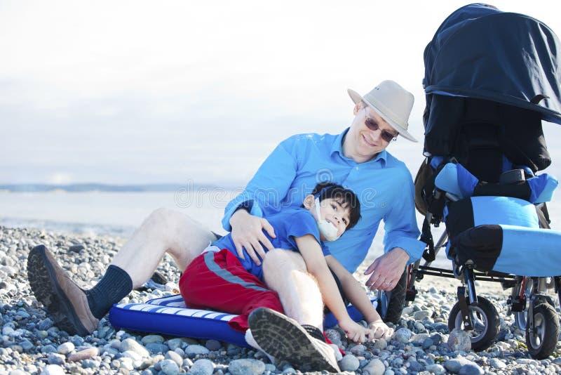 Hervorbringen Sie das Sitzen auf dem Strand, der mit untauglichem Sohn spielt lizenzfreie stockbilder