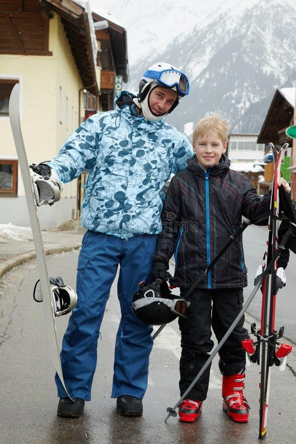 Hervorbringen Sie mit Snowboard und Sohn mit Ski auf Straße lizenzfreie stockfotos