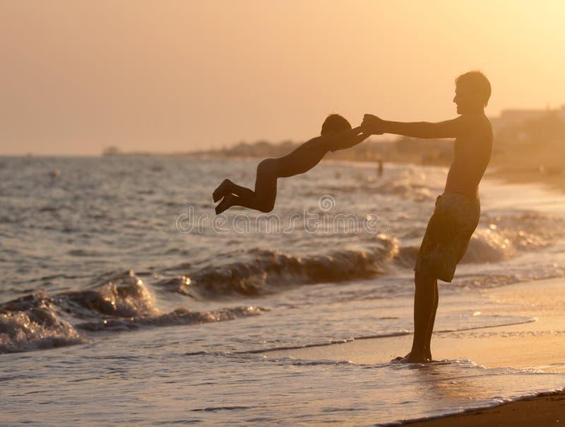 Hervorbringen Sie Spiele mit seinem Sohn auf dem Strand am Sonnenuntergang lizenzfreie stockfotos
