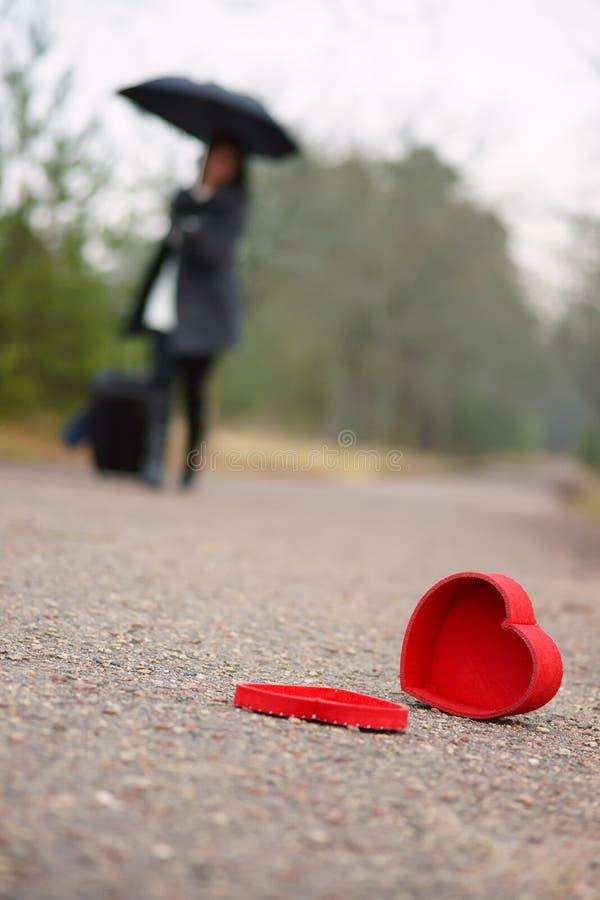 Herz auf der Straße und der Frau mit Gepäck und Regenschirm im Hintergrund stockbild