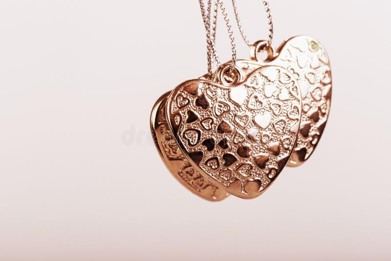 Herz auf Kette Drei goldene Herzen Valentinstag Goldene Herzen für Jungen und Mädchen lizenzfreies stockbild