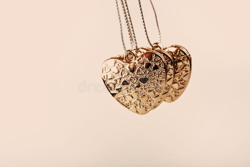 Herz auf Kette Drei goldene Herzen Valentinstag Goldene Herzen für Jungen und Mädchen lizenzfreie stockfotografie