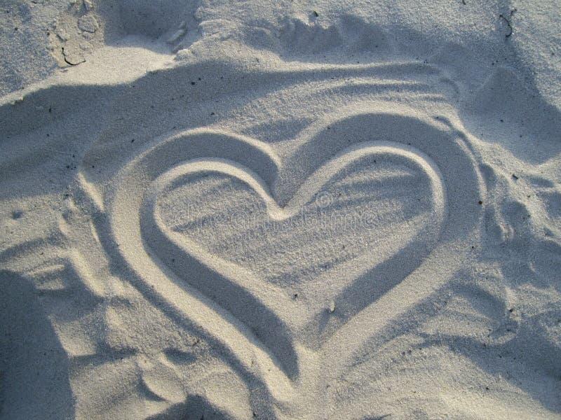Herz auf weißem Sand lizenzfreie stockbilder