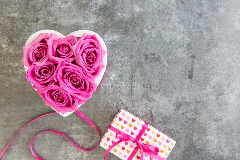 Heart of roses in pink and gift box with bow, Mother`s Day. Grey background, free space for text stock photos