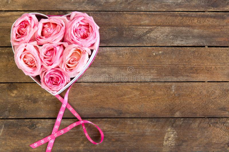 Heart of roses in pink with ribbon on wooden background. Mother`s Day, top view stock photos