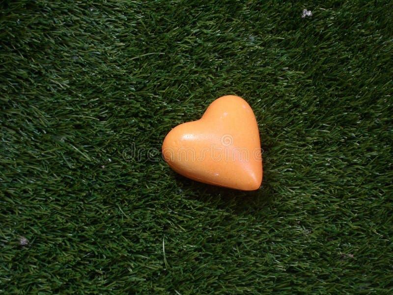 Herz in der Orange auf Hintergrund des grünen Grases lizenzfreie stockfotos