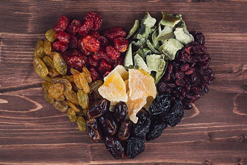 Herz der Trockenfrüchtenahaufnahme auf braunem hölzernem Hintergrund Dekorative Zusammensetzung für Valentinsgruß ` s Tag stockfoto