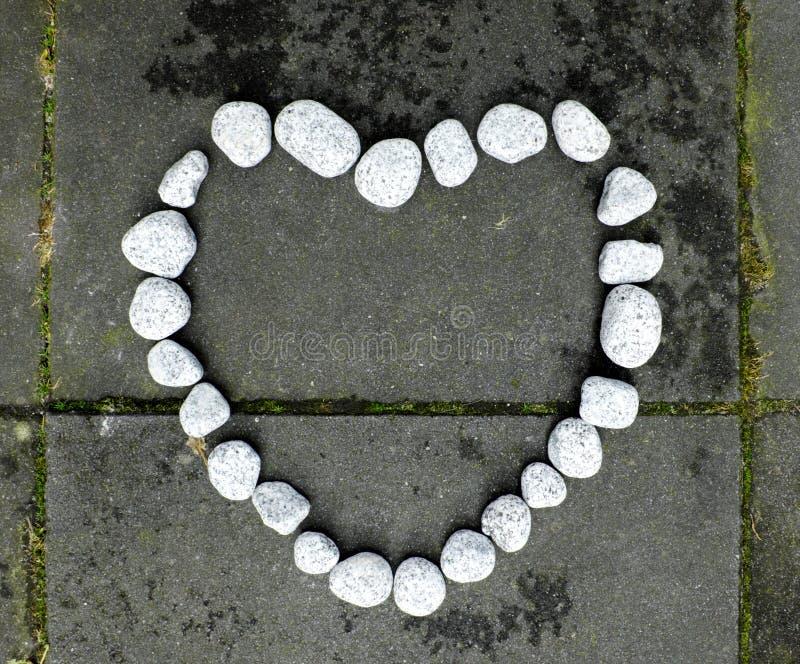 Herz des Steins gemacht von den kleinen weißen Steinen auf dem dunklen Steinhintergrund lizenzfreies stockbild