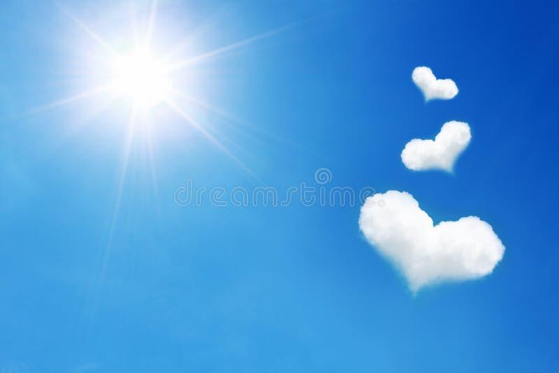 Herz drei formte Wolke auf blauem Himmel mit Sonnenschein lizenzfreie stockfotografie