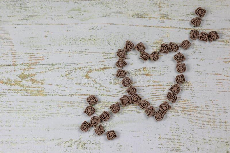 Herz durchbohrte durch einen Pfeil, der von den braunen Rosen gemacht wurde Auf hölzernem Hintergrund Foto oben Fest der Liebe, V stockfoto