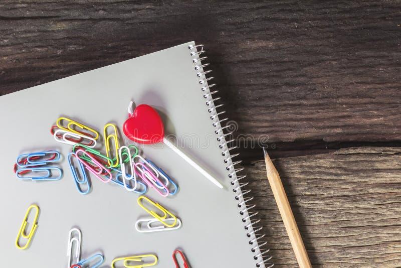 Herz-förmige Kerze mit Notizbüchern, Bleistifte, Büroklammern, auf altem lizenzfreies stockfoto