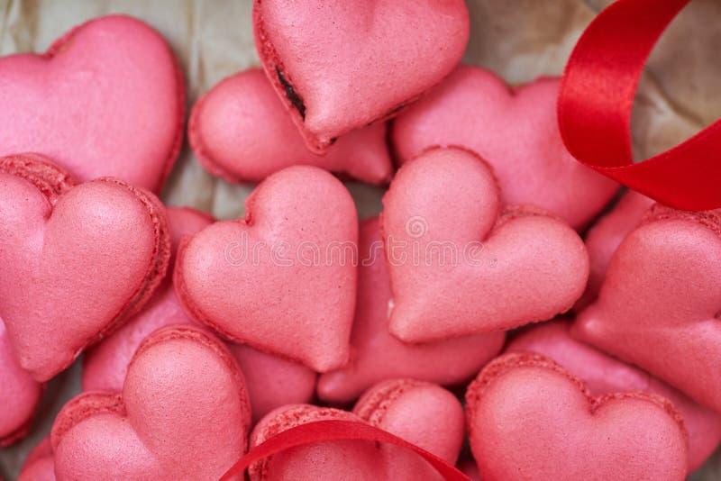 Herz-förmige macarons mit Blumen und Band auf einem Holztisch Kreative Dekoration für Valentinstag lizenzfreie stockfotografie