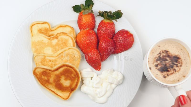 Herz-förmige Pfannkuchen mit Erdbeere auf einem weißen Teller lizenzfreie stockfotos
