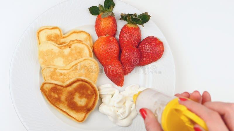 Herz-förmige Pfannkuchen mit Erdbeere auf einem weißen Teller stockfotografie