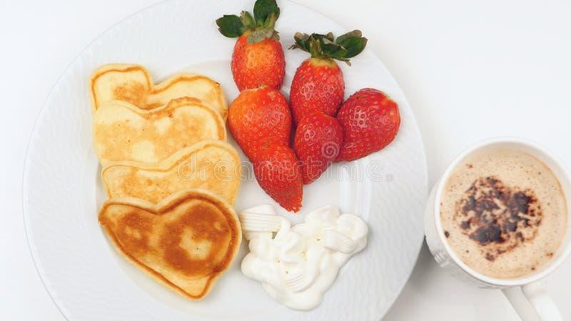 Herz-förmige Pfannkuchen mit Erdbeere auf einem weißen Teller stockbilder