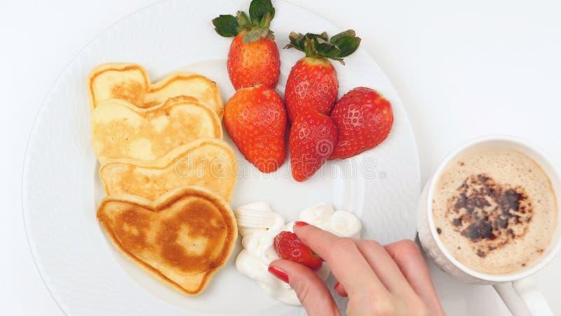 Herz-förmige Pfannkuchen mit Erdbeere auf einem weißen Teller lizenzfreies stockfoto