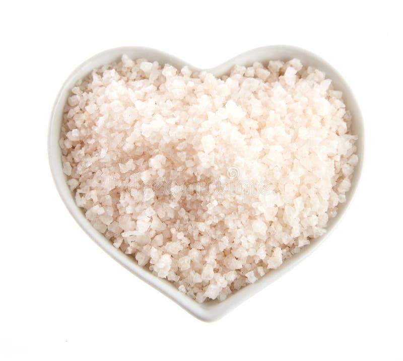 Herz-förmige Schüssel Himalaja-Salz auf Weiß lizenzfreie stockfotos
