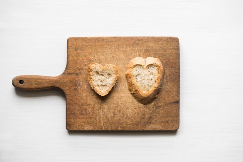 Herz-förmige Scheiben brot auf altem Schneidebrett lieben Konzept stockbild