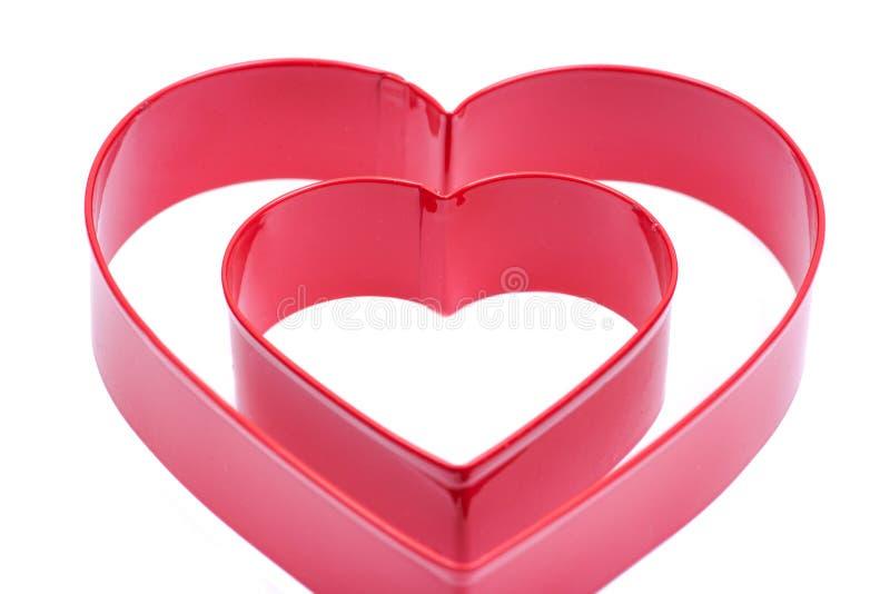 Herz-Form-Höhlen-Kuchen-Schneider-Plastikform für die Plätzchen-Gebäck-Nachtisch-Backen-Verzierung lokalisiert auf Weiß lizenzfreie stockfotografie